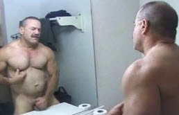 Muscular mature masturbates in front of the mirror