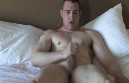 Big and muscular guy masturbates on bed