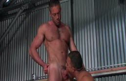Two muscular men have anal sex in a warehouse