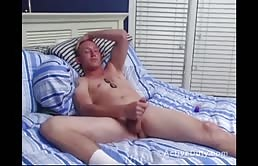 Shy guy strokes his cock on bed